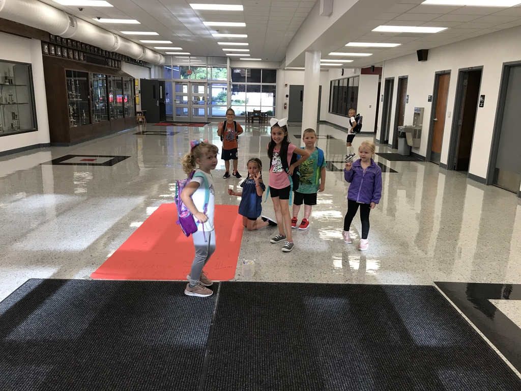 This is an image of students signing the red carpet on the first day of school.