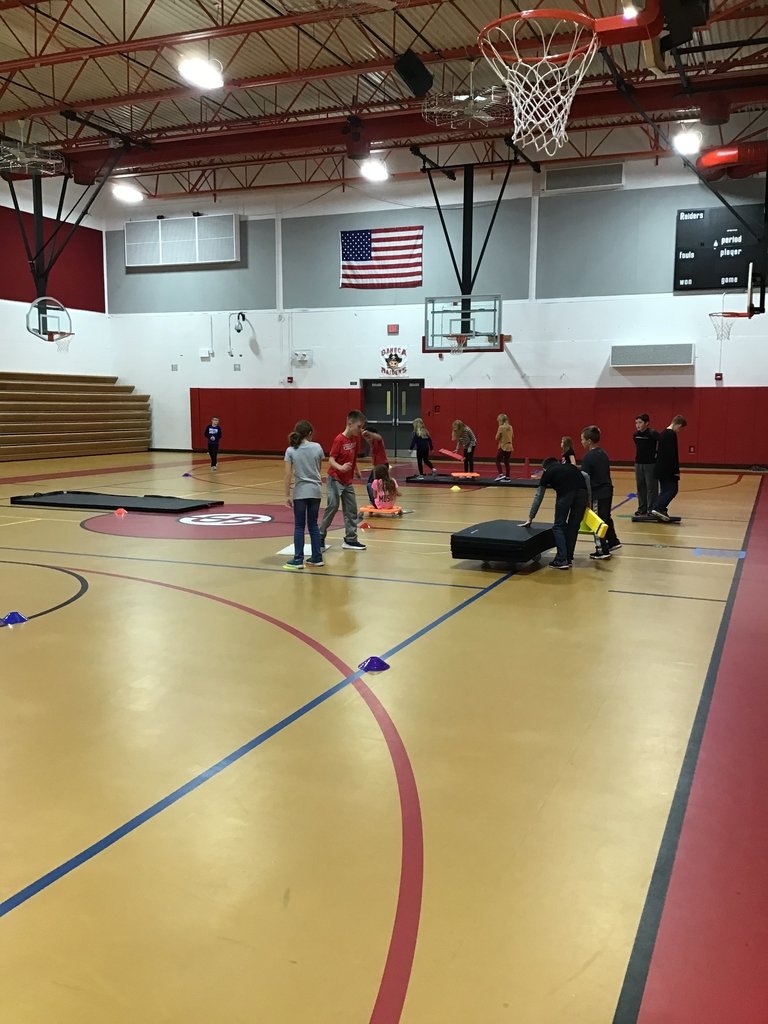 "4th grade students playing the game ""Raging River"" in physical education class. Students must cross the ""river"" using the equipment they are given without having any body part touch the floor directly."